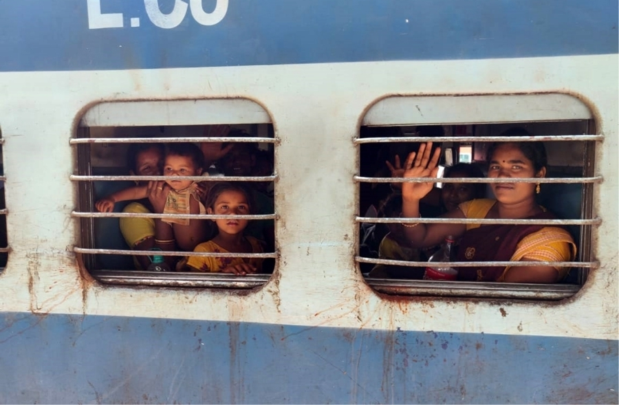 Indian women and chindren looking out of barred windows